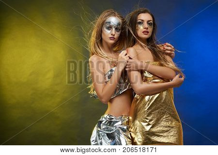 Photo of two girls with stunnng figures and long, straight hair. They wear fantastic make-ups, made by an artist ic silver and golden tones. Their bodies are young and healthy.