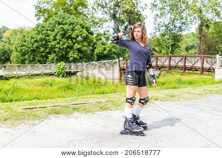 Young woman rollerskating or roller skating outside in summer park with knee and elbow pads posing by bridge