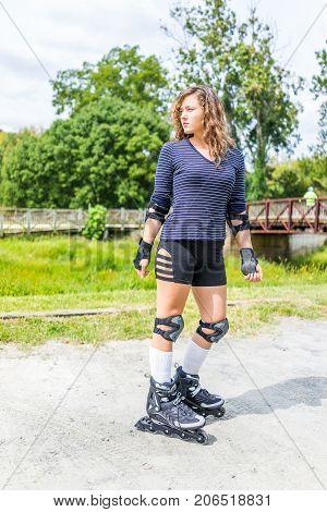 Young woman rollerskates or roller skates outside in summer park with knee and elbow pads looking by bridge