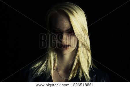 young woman turning into a vampire on a black background