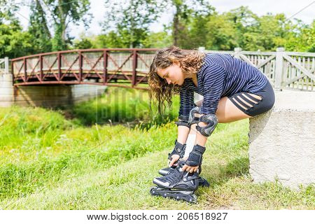 Young woman sitting with rollerskates or roller skates outside in summer park with knee and elbow pads and securing shoes