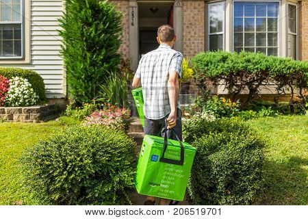 Fairfax USA - September 12 2017: Amazon Fresh insulated grocery delivery bags totes on front home house porch closeup with man carrying