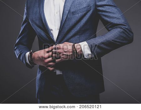 portrait of handsome fashion stylish hipster businessman model dressed in elegant blue suit posing on gray background in studio. Buttoning his jacket