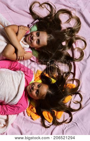 Childhood And Love Concept. Girls On White And Pink Sheets