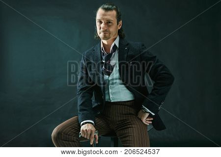 The mature stylish man in a suit on a gray studio background. Businessman sitting on an armchair
