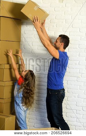 Daughter Puts Hands Up And Father Puts Boxes In Pile