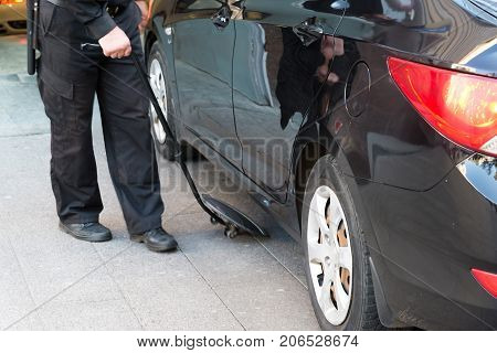 The guard examines the bottom of the car with a mirror