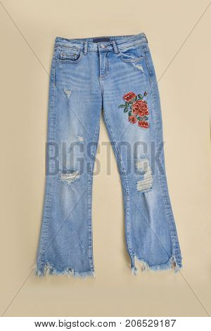 Embroidered flowers Torn Jeans - beige background