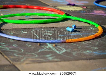 Colourful chalk and hula hoops lay on playground.