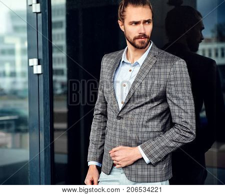 portrait of sexy handsome fashion male model man dressed in elegant checkered suit posing near dark blue reflecting mirror in the street background