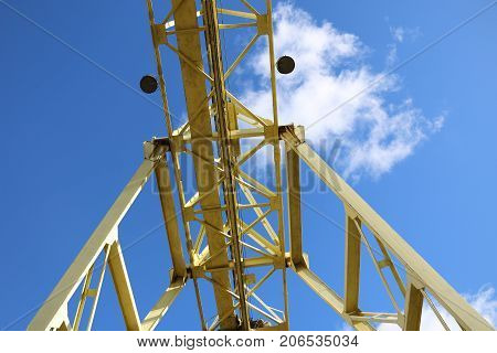 A Large Gantry Crane Made Of Metal Colored Yellow In The Background Of A Bright Blue Sky With Clouds