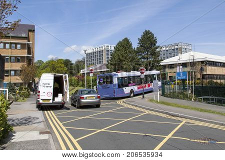 Swansea, UK: May 04, 2016: Traffic congestion and a white delivery van parked on double yellow lines at Singleton Hospital. A bus is passing through the barrier between the hospital and university