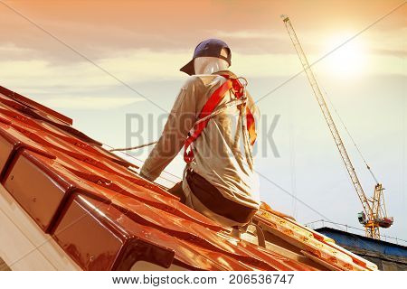 Roof repair men model worker replacing tiles on the roof house with sunlight background