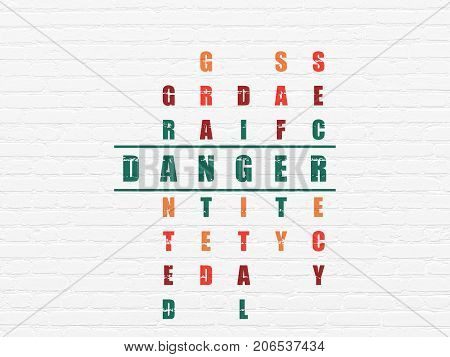 Protection concept: Painted green word Danger in solving Crossword Puzzle