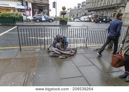 Edinburgh, UK: June 27, 2016: A beggar sits in the rain on a busy junction in Edinburgh. It is raining and he is being ignored by passersby. Begging is illegal under the Vagrancy Act of 1824.