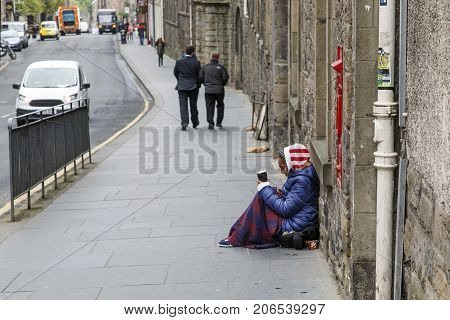 Edinburgh, UK: June 26, 2016: A female beggar sits on a busy road in Edinburgh. She is holding a cup and being ignored by passers by. Begging is illegal under the Vagrancy Act of 1824.