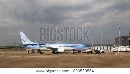 Cardiff, UK: May 29, 2016: A Thomson Holidays airplane awaiting baggage loading at Cardiff Airport. Thomson are a UK based holiday travel operator.