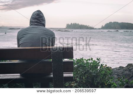 Sad And Lonely Man Sitting On Bench Overlooking Sea On Vancouver Island