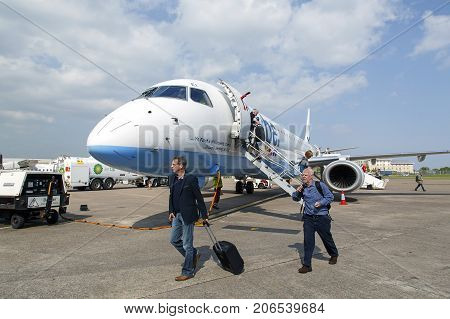 Cardiff, UK: May 29, 2016: Two male passengers disembark from a scheduled flight from Edinburgh. Flybe is the largest independent regional airline in Europe and is based in Exeter.