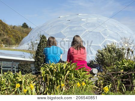 St Austell, UK: April, 2016: Two lady visitors sit facing away from the camera, looking of one of the biomes at the Eden Project. Inside the biomes plants from many diverse climates and environments.