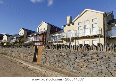 Swansea, UK: March 31, 2016: A large five bedroom individually designed family house with balcony and stone wall. Prices of desirable detached houses in prime locations have escalated enormously in the last decade.