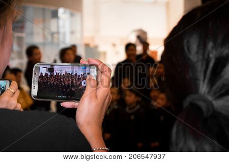 VICTORIA GARDENS BANGKOK THAILAND - SEPTEMBER 10: An unidentified woman films the with a Samsung smartphone on September 10 2017 in Bangkok.