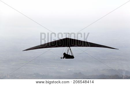 Silhouette Of A Man Flying High With His Hang Glider