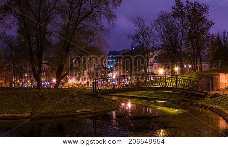 Night view of park pond and bridge in Yusupov Garden and illuminated Sadovaya Street Saint Petersburg Russia