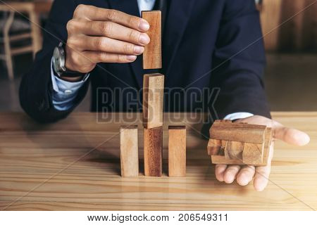 Businessman hand arranging stacking wooden blocks development as step stair Business growth success process Growth concept with wooden blocks plan and strategy in business.