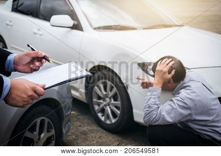 Traffic Accident and insurance concept Insurance agent working on report form with car accident claim process.