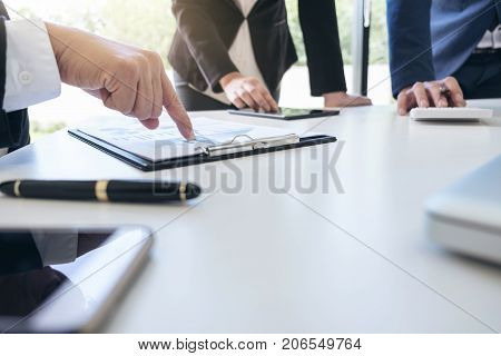 Teamwork process Business team managers colleagues discussing and analysis new plan financial graph data and marketing documents report on office table with laptop and digital tablet.