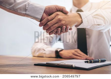 Real estate broker agent and customer shaking hands after signing contract documents for realty purchase Bank employees congratulate Concept mortgage loan approval.