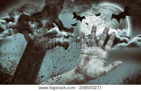 Digital image of silhouette bat against hand by side of celtic cross in front of moon