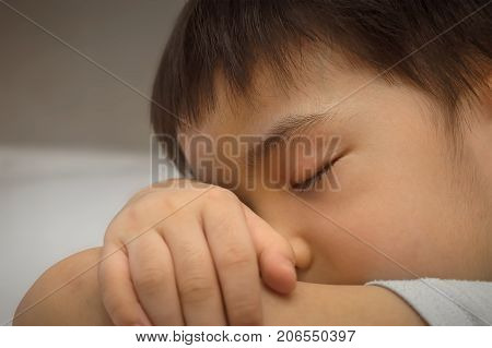 Boy Takes a Nap with Head Down