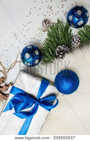 Christmas festive background of presents. Wrapped in silver paper gift box, ornament blue balls and strobila with fur and pine, top view with copy space. Congratulation and handmade decor concept