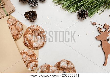 Festive background of Christmas and New Year gift. Decoration from sweet cakes near decoration from pine branch and wooden deer ornament, top view. Holidays, congratulation and home baking concept