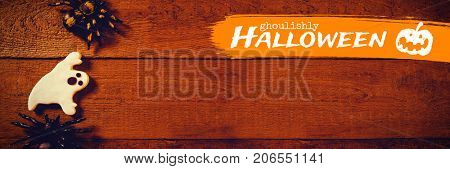 Graphic image of ghoulishly Halloween text against overhead view of decoration with cookie on table