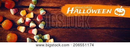 Graphic image of ghoulishly Halloween text against overhead view of colorful sweet food on table