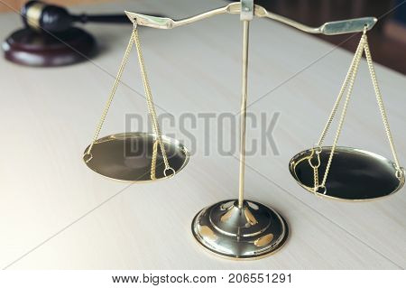 Close up of scales of justice and gavel on wooden table in a courtroom striking Law and justice concept.