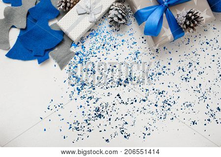 Background of New Year decor and gifts top view. Wrapped in silver paper presents, ornament blue balls and felt fir tree with tinsel spread around, copy space beneath. Handmade decoration concept