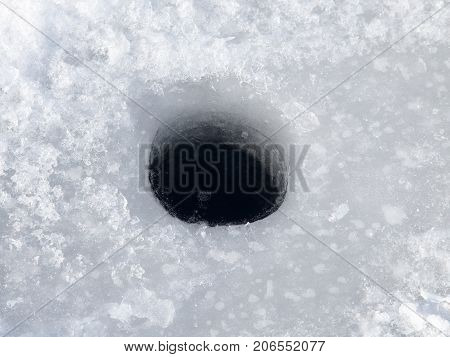 hole on the ice . In the park in nature