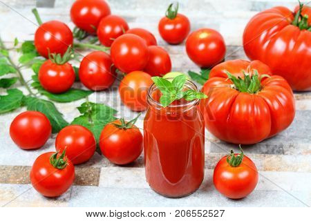 Homemade preserved ketchup from giant beefsteak and common tomatoes in a bottle. Fresh tomatoes and tomato leaves are around a bottle.