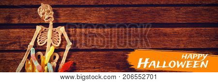 Digital image of happy Halloween text against view of skeleton decoration with candies on table