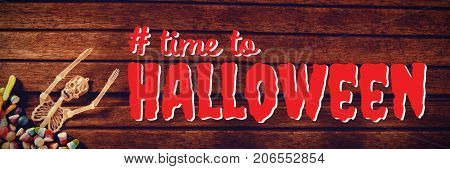 Digital composite image of time to Halloween text against skeleton decoration with candies on wooden table