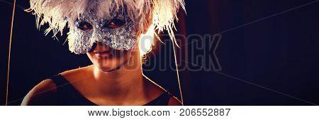 Portrait of woman in masquerade mask and wig at stage