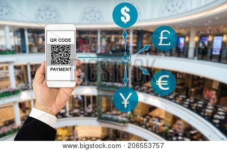 QR code payment concept : Hand wearing business suit holding smartphone display QR code on screen with blurred background of shopping mall. Various currency icons implying payment can be in any currency.