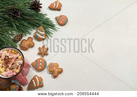 Festive Christmas and New Year backdrop. Green pine, sweet gingerbread cookies and cup of marshmallows on white background, top view free space on right. Greetings and congratulation concept