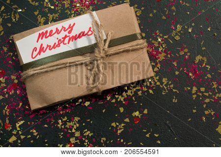 Festive backdrop of Christmas present. Wrapped paper gift bag with handwritten greeting memo on black sparkled background, top view and free space. Happy holiday and congratulation concept