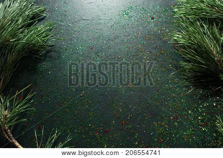 Festive backdrop for Christmas gift and greeting. Top view holiday sparkled and black glittering background with pine, free space. Celebration, presents and congratulation concept