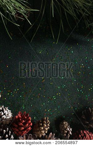 Festive backdrop for Christmas gift and greeting. Top view holiday sparkled and black glittering background with pine and strobilas, free space. Celebration, presents and congratulation concept